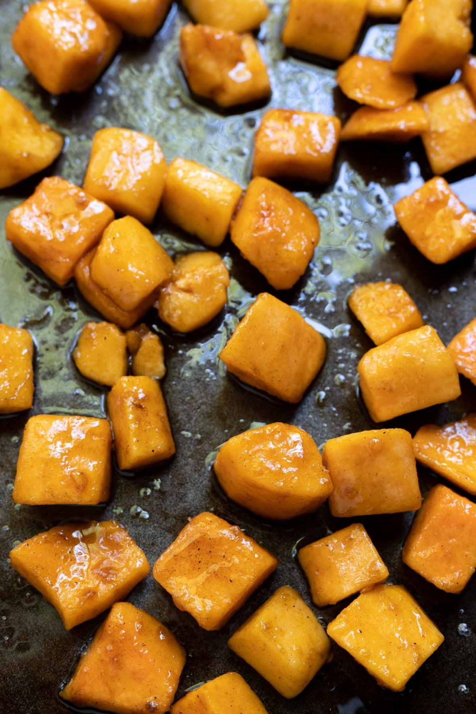 raw butternut squash chunks tossed with oil and sugar on greased sheet pan