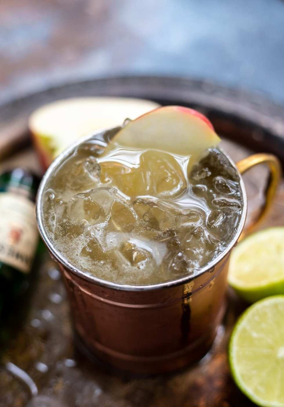 copper cup filled with drink, ice and apple slice