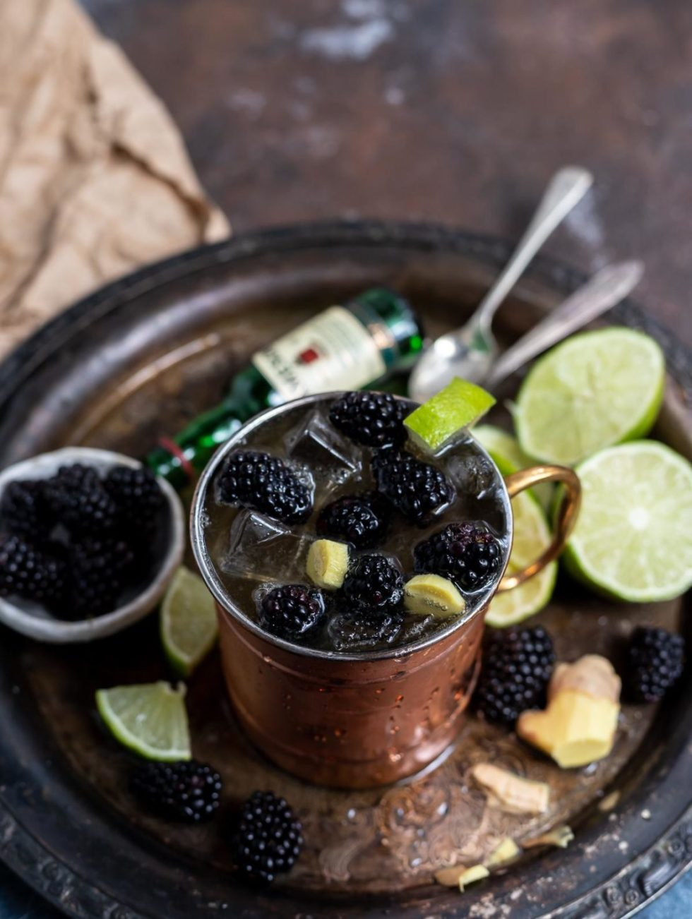 blackberry Moscow Mule in copper cup next to lime and blackberries