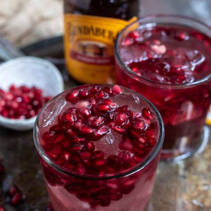 clear glasses with beverage topped with pomegranate seeds