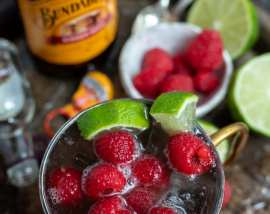 drink in copper mug next to fresh raspberries, limes and ginger beer bottle