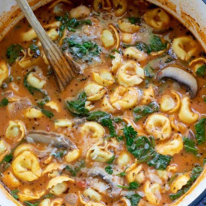 soup filled with tortellini and spinach in pot with wooden spoon