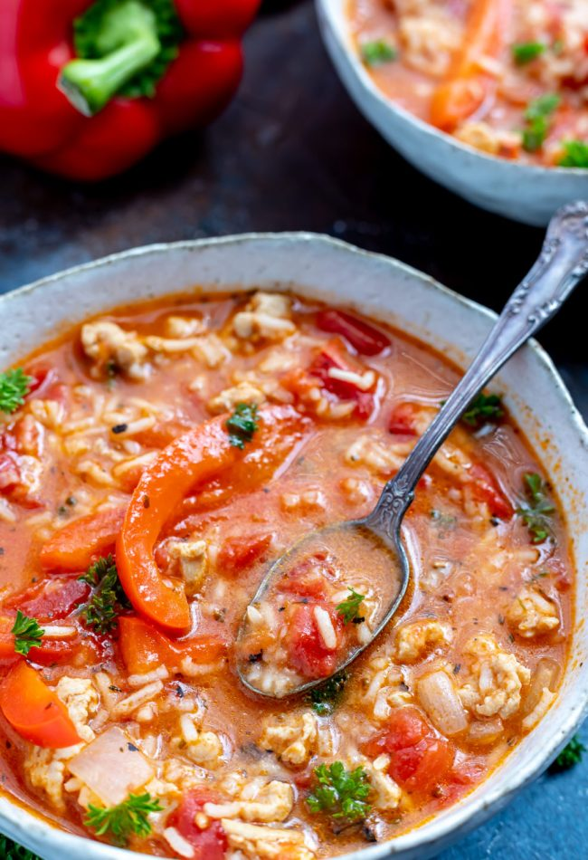 red bell pepper soup in white bowl with silver spoon