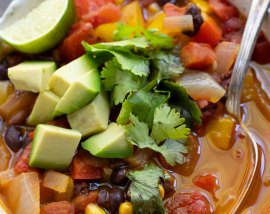 enchilada soup topped with avocado and cilantro in white bowl