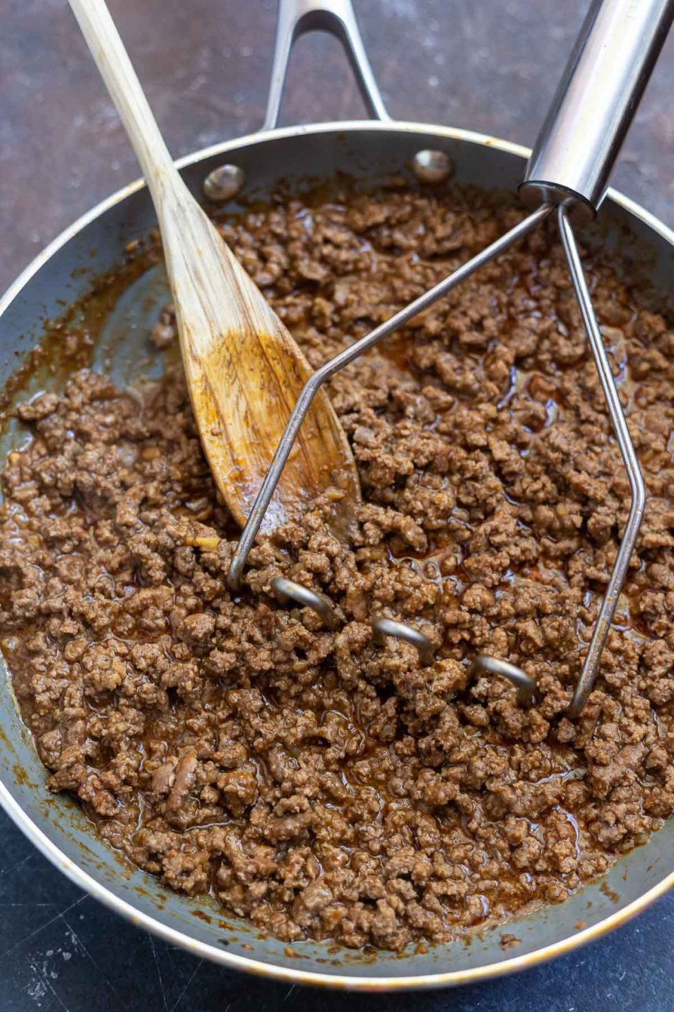 saucy ground beef taco meat in pan with wooden spoon and potato masher