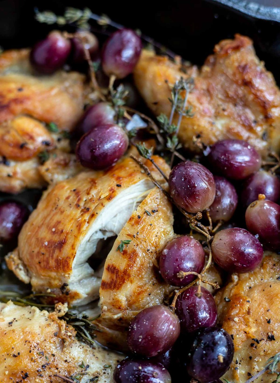 cooked chicken thigh sliced open next to roasted grapes
