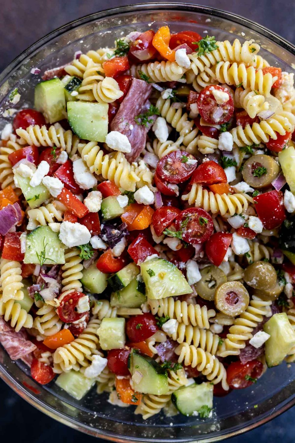 greek pasta salad prepared in clear glass bowl