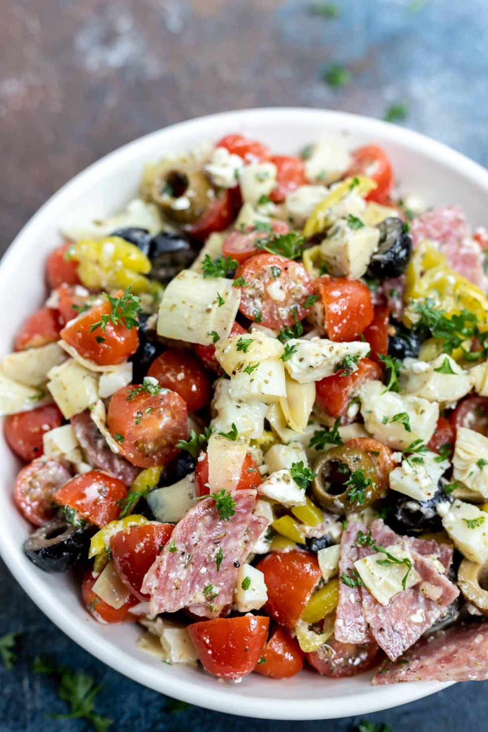 meat cheese and veggie salad in white bowl