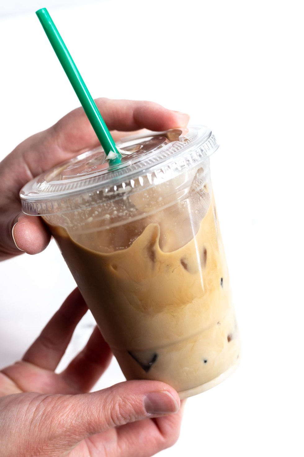 hand holding plastic cup filled with creamy coffee
