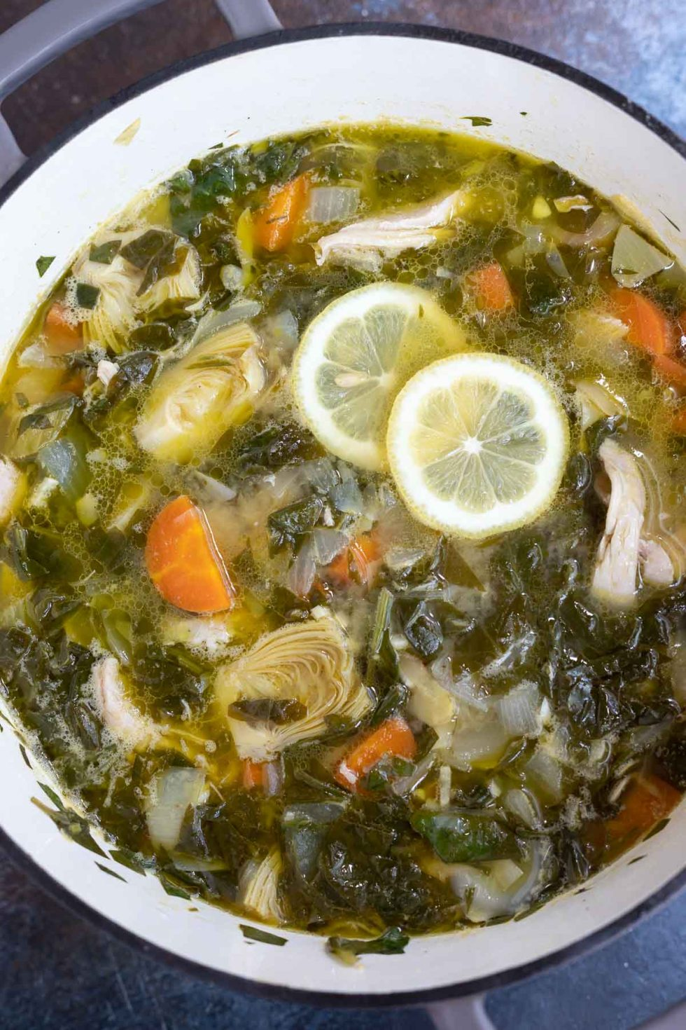 spinach artichoke lemon chicken soup in pot with sliced lemons on top