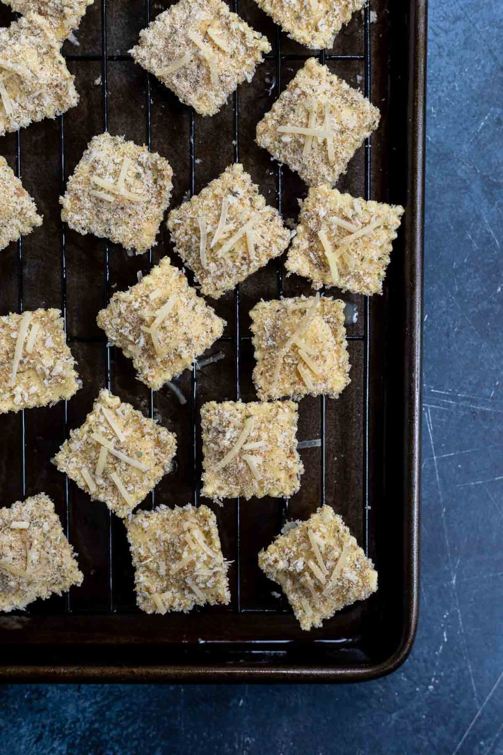 prepared uncooked breaded ravioli on rimmed baking sheet with wire rack