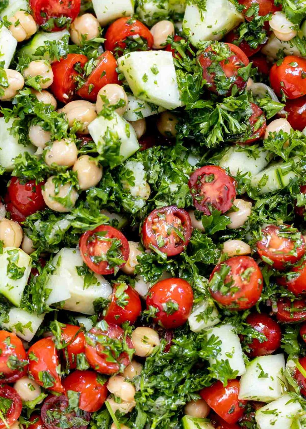 close up of tomatoes, cucumbers and chickpeas tossed in fresh herb dressing