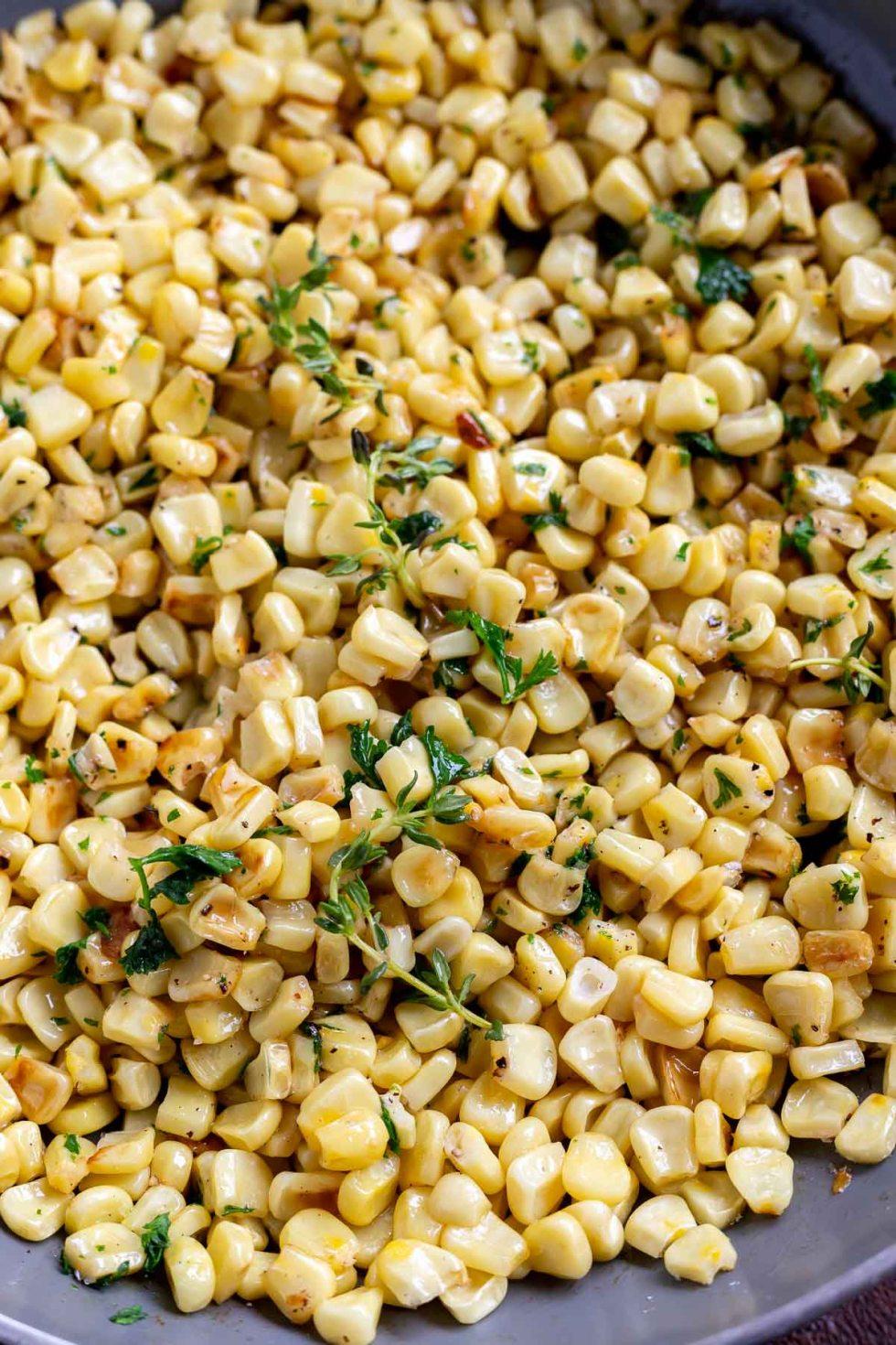 yellow corn and green fresh thyme in pan