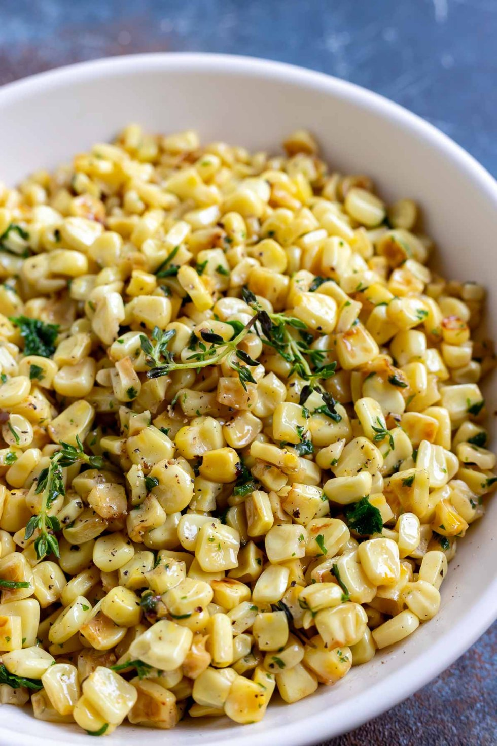 yellow corn with green thyme served in white bowl