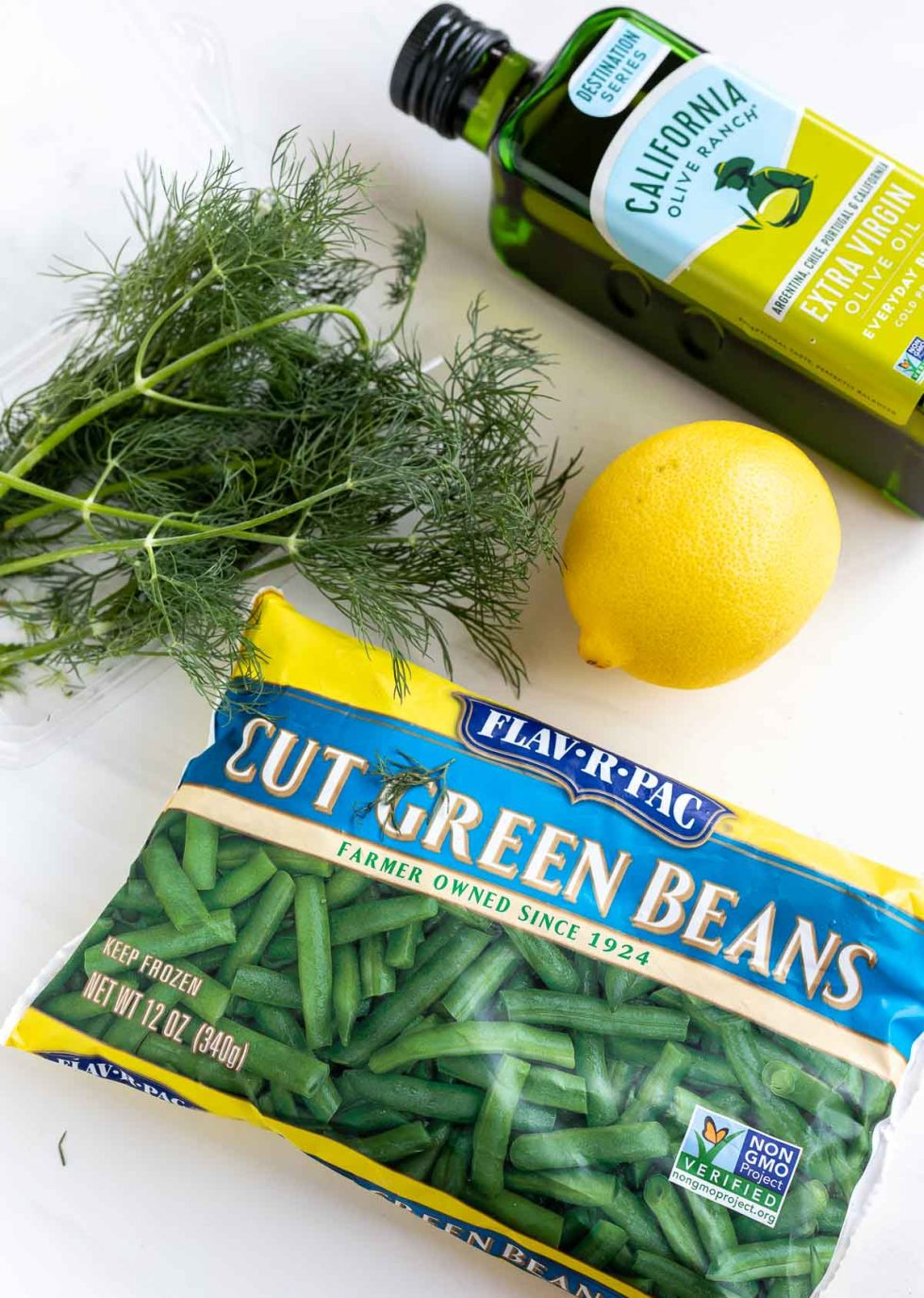 bag of frozen green beans, lemon, fresh dill and bottle of olive oil