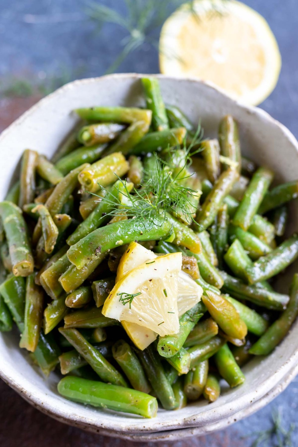 green beans and lemon slices served in white bowl