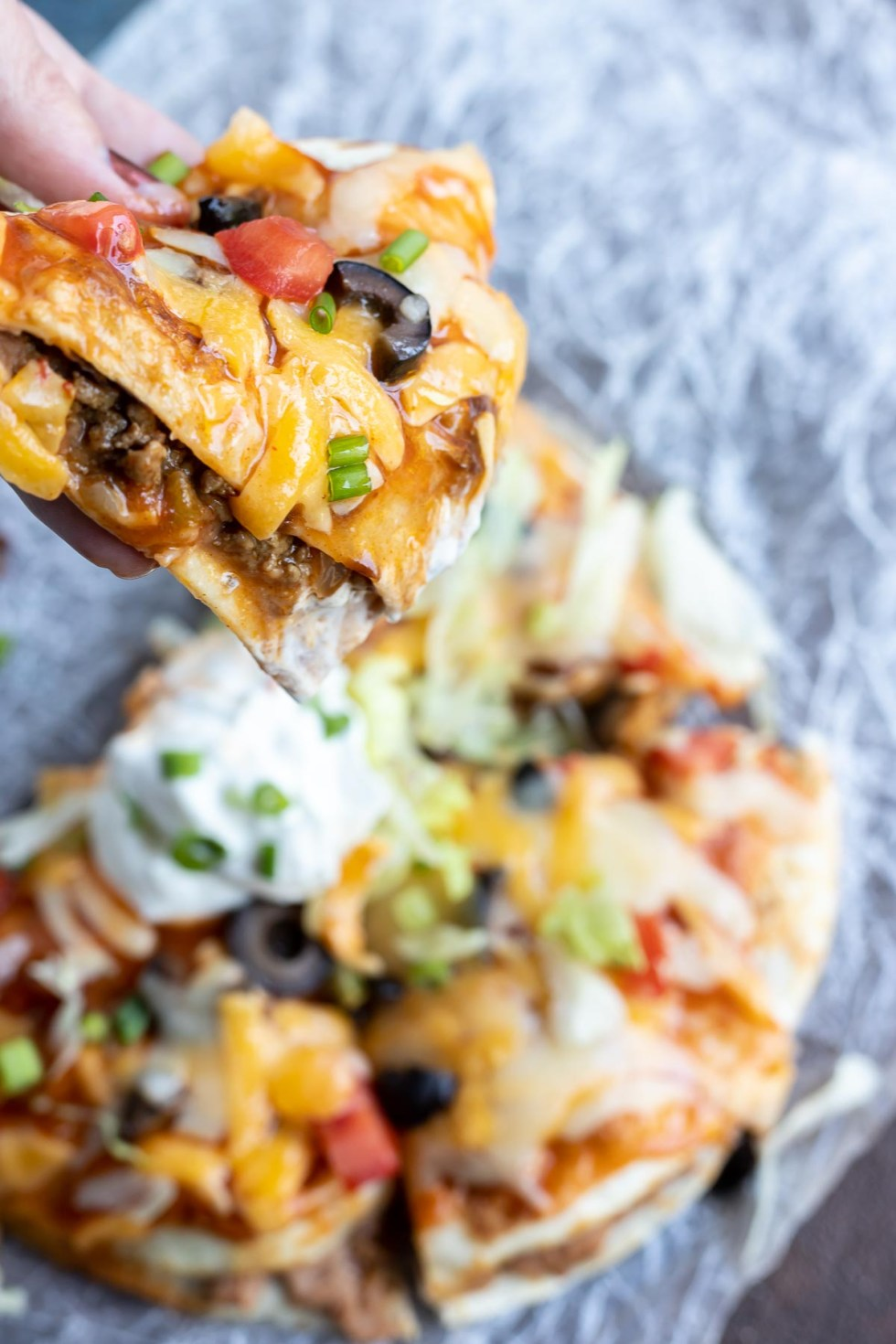 hand holding slice of Mexican pizza