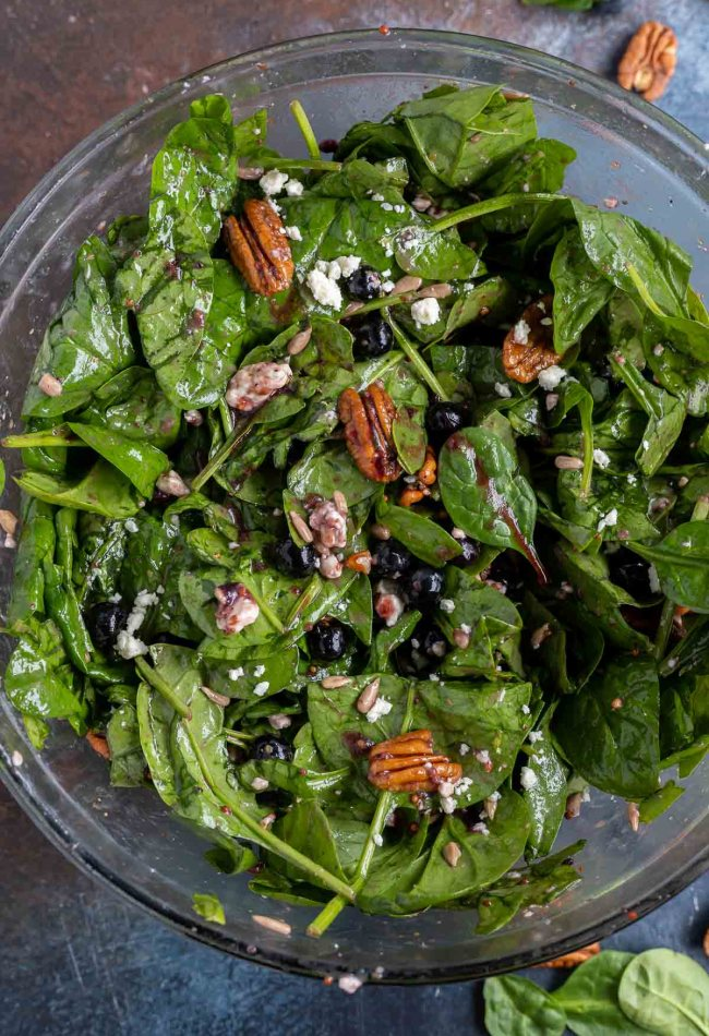 prepared spinach salad in clear glass bowl