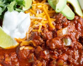 meat chili topped with sour cream, avocado, cheese and limes