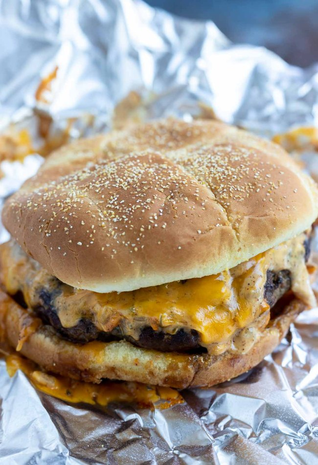 cooked prepared cheeseburger on tin foil