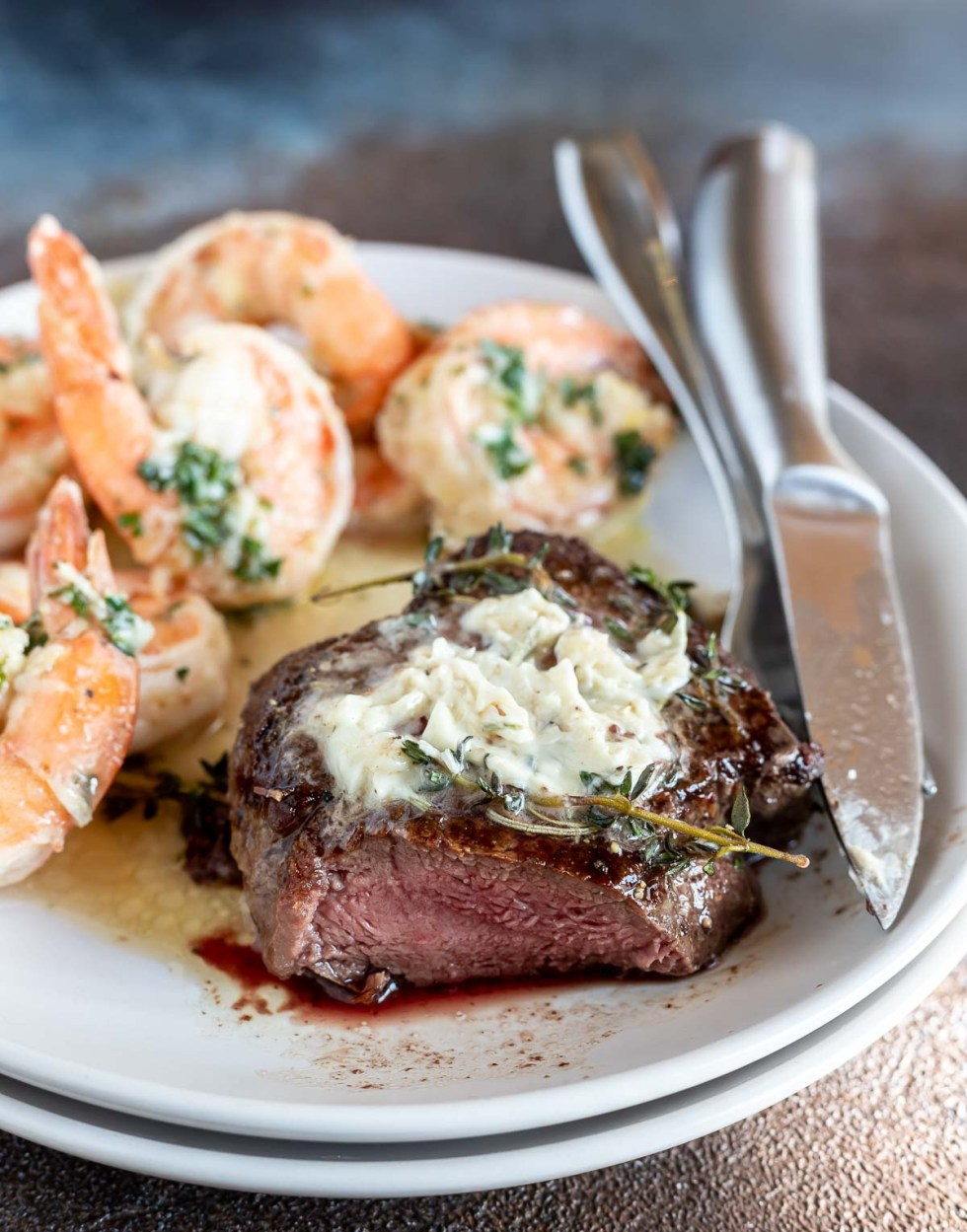 butter topped steak with slice cut out served next to shrimp on white plate