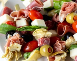 meat, cheese, olives and tomatoes on skewers served on white plate