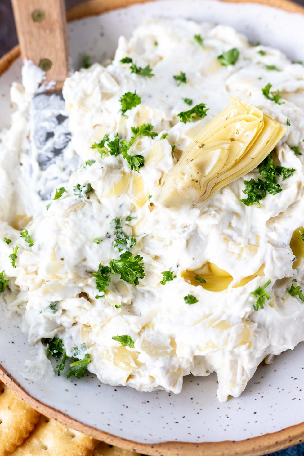 creamy dip topped with an artichoke heart and chopped parsley