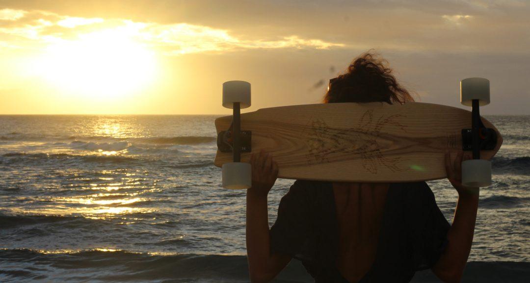 Couché de soleil face à la mer avec un skateboard