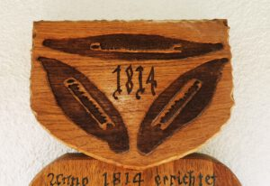 Briefkasten mit Hausgeschichte und Wappen.