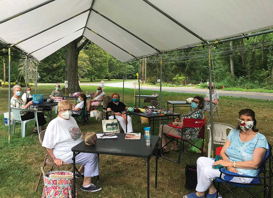 Members of the Woodbridge Center craft group gather at the white canopy by the Woodbridge Library