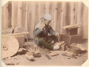 1898. Japanese tradesman holding geta between his feet while he chisels.