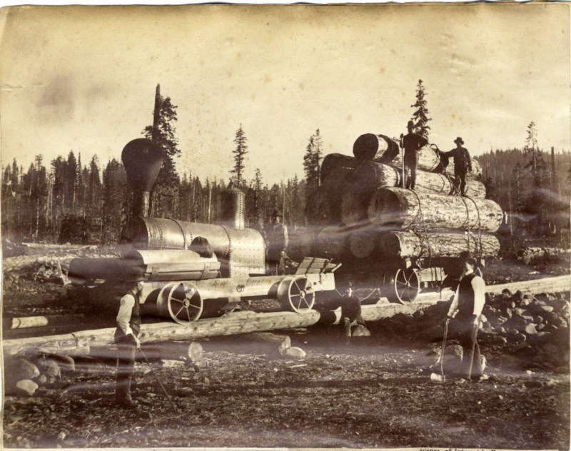 View of a steam engine and wagon hauling a load of logs.
