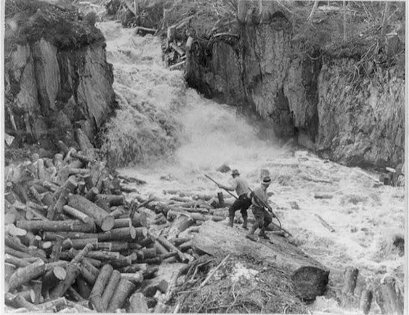 Log drivers sorting in heavy rapids.