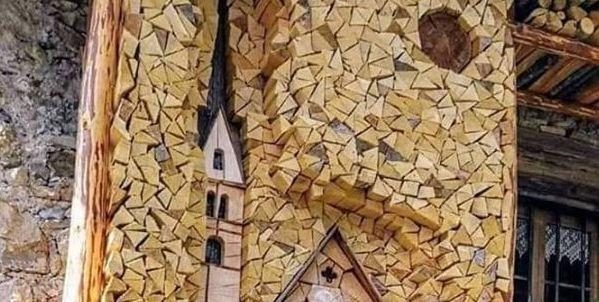 Wood pile art of a church.