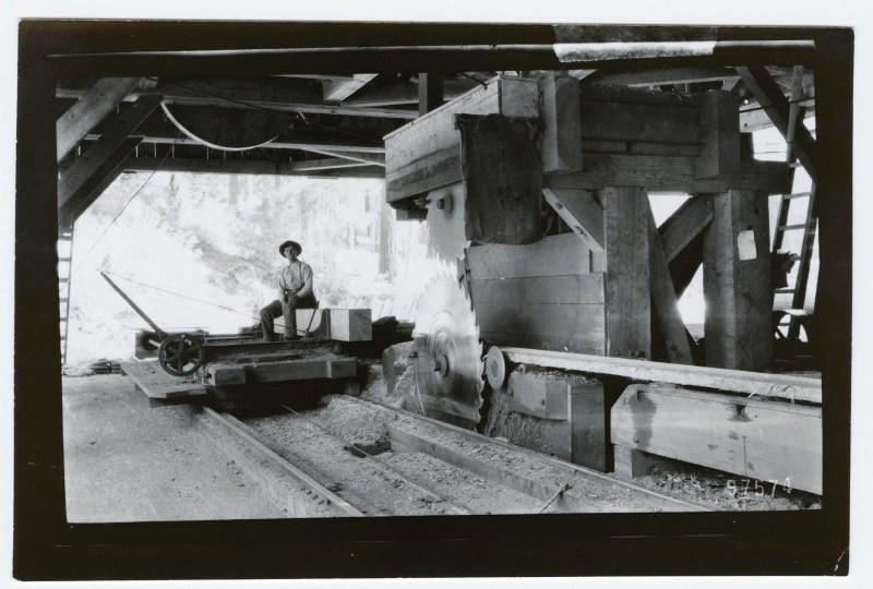 1900 man sitting near large saw blade