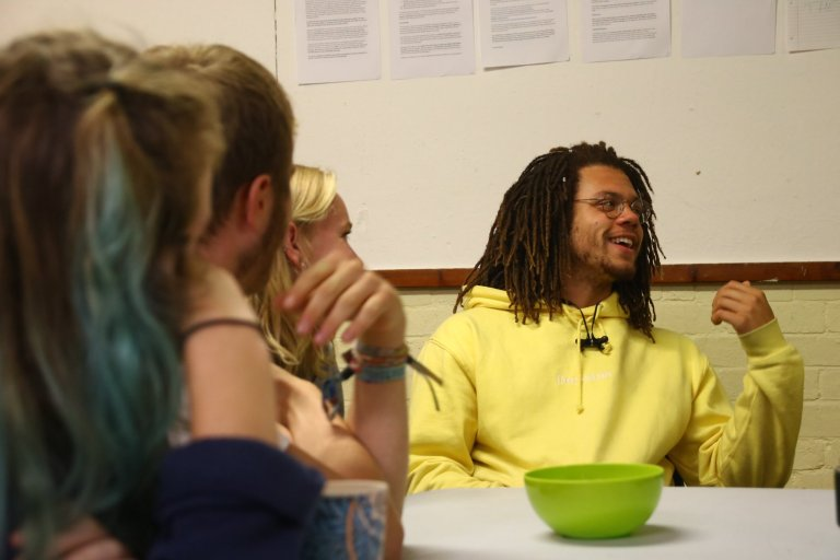 young man in a yellow hoody talking at a meeting