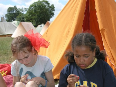 two children making friendship bands in front of a tent