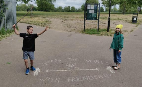 two children standing either side of a 2m distance sign