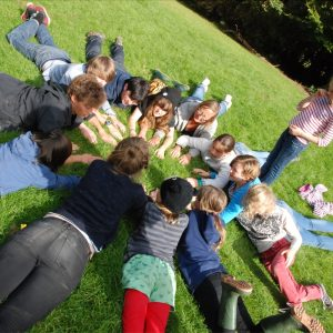 A mixed group of children and adults form a circle, lying on a grassy field. Their hands are together towards the centre of the circle