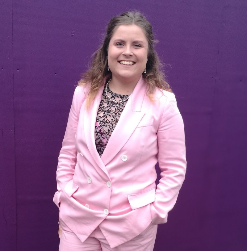 Image shows Aggie smiling towards the camera, dressed in a pale pink business suit.