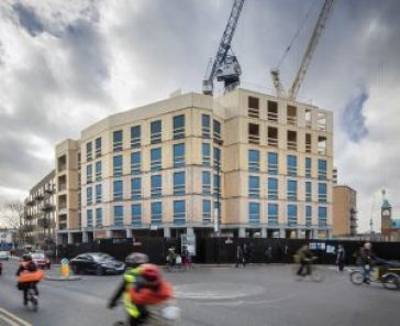 Multi storey cross laminated timber building during construction showing cranes lifting panels into place