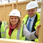 Photos of two smiling people wearing hard hats and high visibility jackets on a construction site holding part of a timber frame wall construciton
