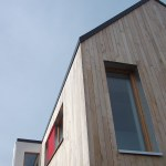Edge of timber clad house with red windows and blue sky