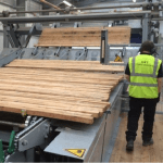 Person in high viability jacket standing to a timber grading machine
