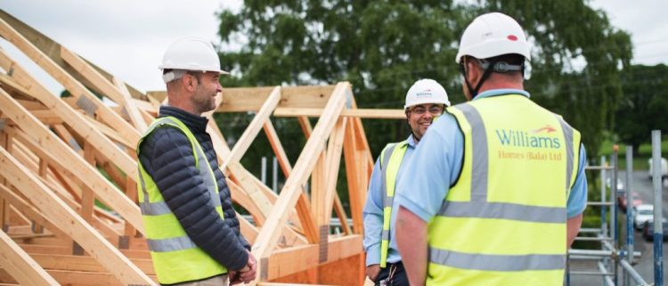 3 people on a building site showing timber roof trusses in place