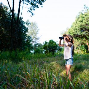 Girl using binoculars in the forest