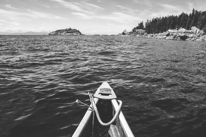 Black and white photo of a bow of a canoe on the Pacific Ocean. The shoreline is seen from a distance.