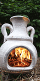 firewood logs burning on a patio chiminea
