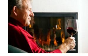 man relaxing by log fire