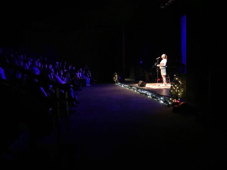 Singer on a darkened theater stage